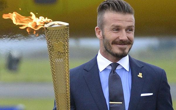 Дэвид Бекхэм держит Олимпийский огонь фото
